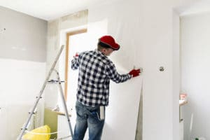 Contractor gluing wallpapers onto a white background during a home renovation project