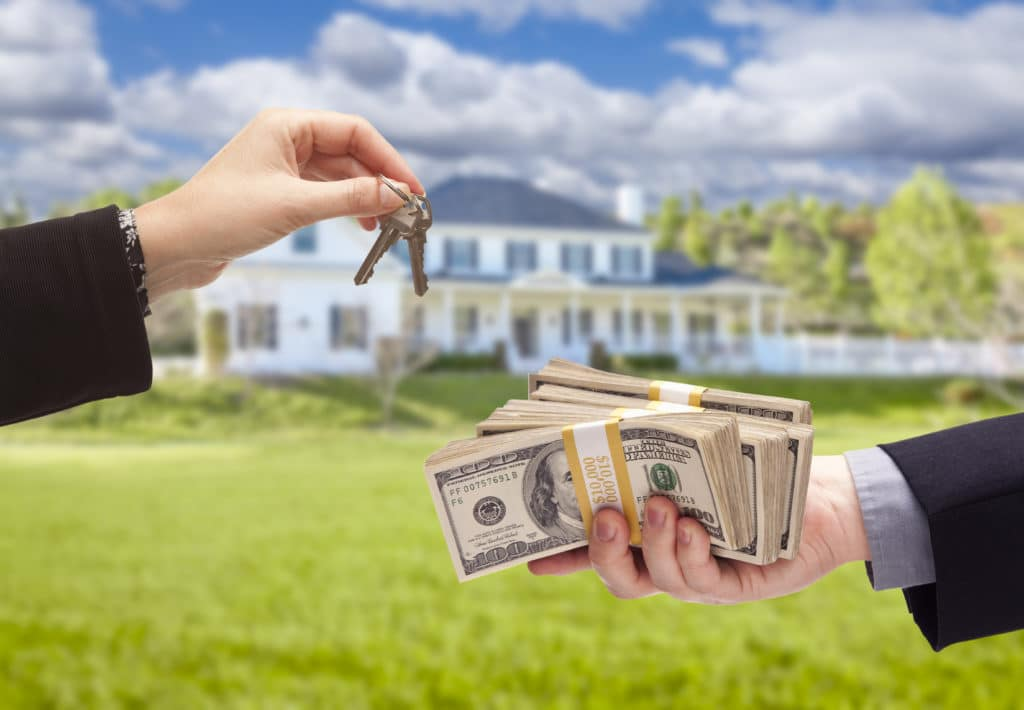 a hand handing over keys while another hand has a handful of cash with a home in the background
