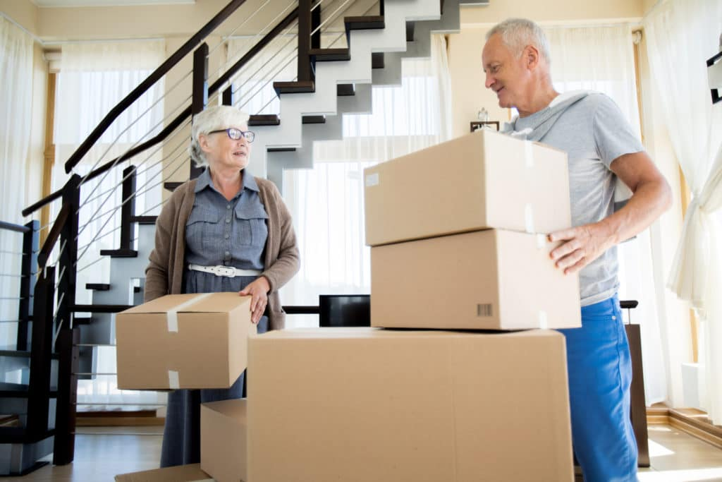 Portrait of happy senior couple packing cardboard boxes while moving to new house