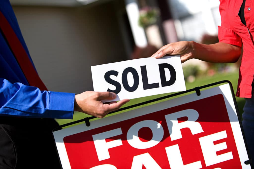 A for sale sign in front of a home with two people handing each other a sign that says sold